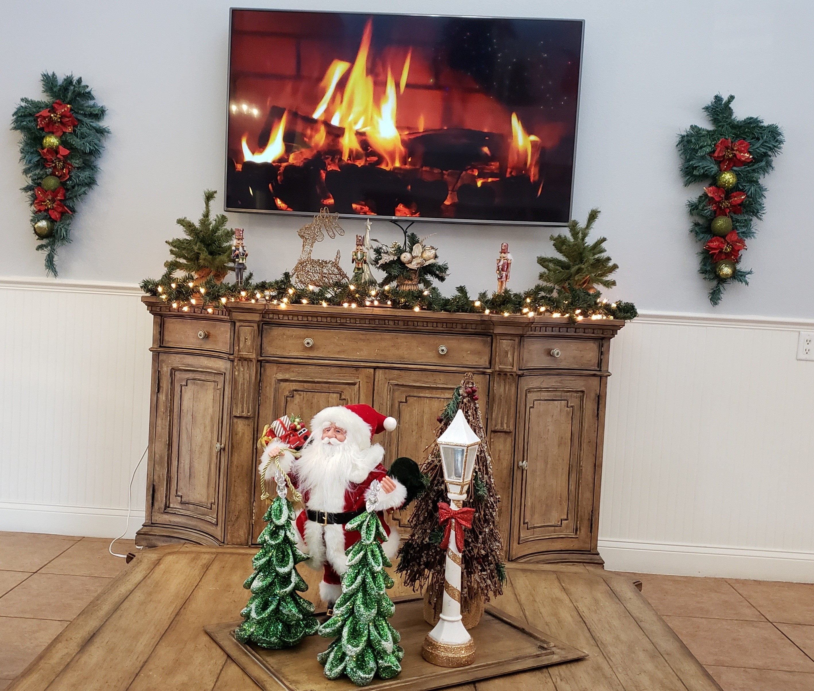 Inside Clubhouse with Christmas Decorations and TV with fireplace on it